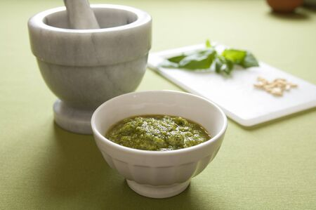Close-up view of organic italian traditional Pesto sauce in a bowl with basil, pine nut, olive oil and mortar Stock Photo - 17825165