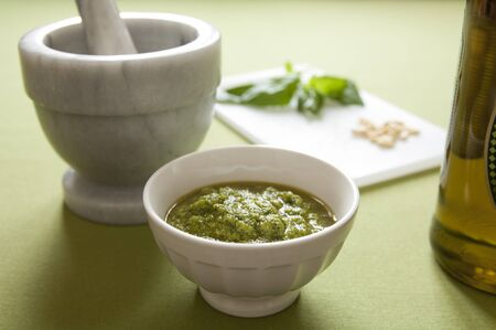 Close-up view of organic italian traditional Pesto sauce in a bowl with basil, pine nut, olive oil and mortar Stock Photo - 17824812