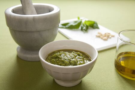 Close-up view of organic italian traditional Pesto sauce in a bowl with basil, pine nut, olive oil and mortar