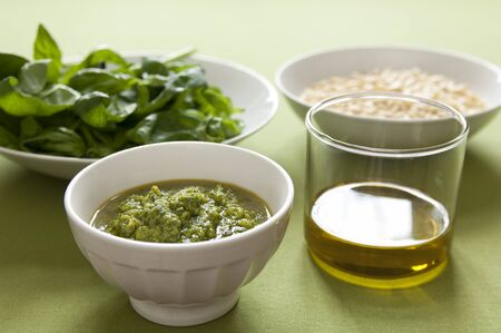Close-up view of organic italian traditional Pesto sauce in a bowl with basil, pine nut and olive oil Stock Photo - 17825197