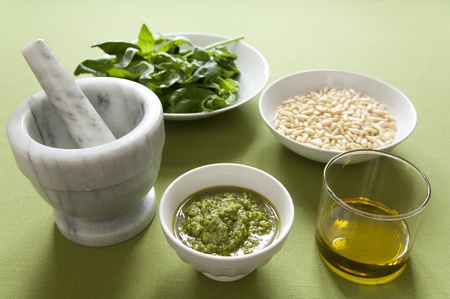 Close-up view of organic italian traditional Pesto sauce in a bowl with basil, pine nut and olive oil Stock Photo