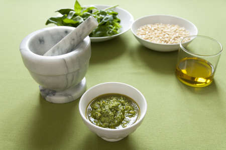 Close-up view of organic italian traditional Pesto sauce in a bowl with basil, pine nut and olive oil Stock Photo - 17824630