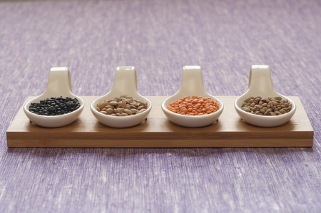 Close-up view of four different variety of Organic Lentils   left to right  Black Beluga, Green, Red, Small Umbrian Lentils  Stock Photo