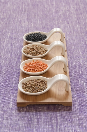 Close-up view of four different variety of Organic Lentils   back to front  Black Beluga, Green, Red, Small Umbrian Lentils  Stock Photo