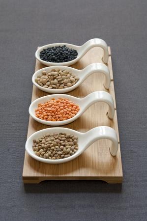 Opini�o do Close-up de quatro variedade diferente de lentilhas org�nicos tr�s para a frente Beluga Preto, Verde, Vermelho, Pequeno �mbria Lentilhas Banco de Imagens