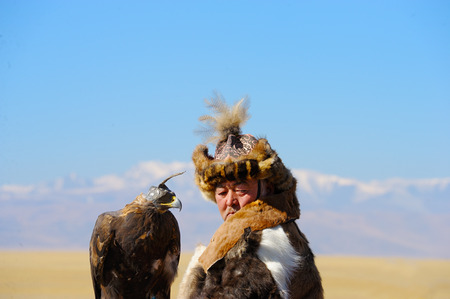 russia steppe: Kosh-Agach,Russia - September 21, 2014: the hunter with an eagle at the festival: Berkut-wing Chu steppe