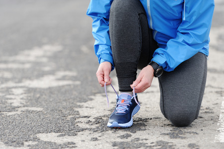 tightening: Woman runner tying laces before training. Marathon