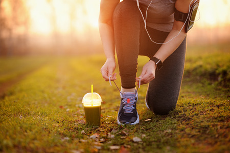 Green detox smoothie cup and woman lacing running shoes before workout. Fitness and healthy lifestyle concept.