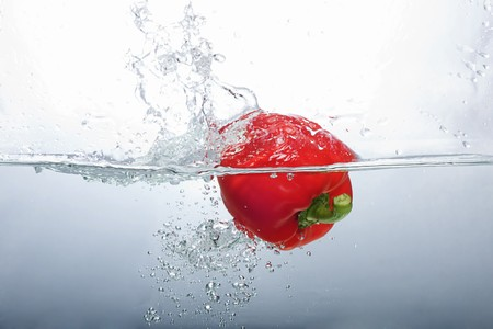 Fresh Red Bell Pepper splashing into water photo