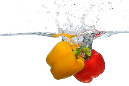 Fresh yellow and red Bell Pepper splashing into water