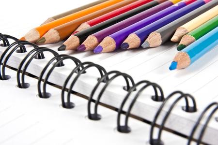 Color pencils in arrange in color wheel colors on note book photo