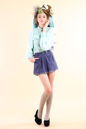 Fashion model in spring light blue and purple clothes on beige background  photo