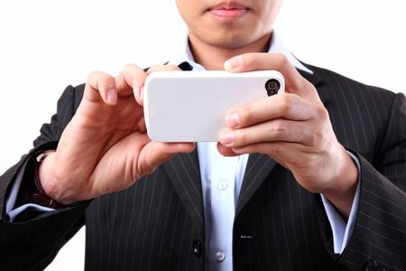 celulas humanas: Hombre de negocios asi�tico con una c�mara m�vil en el fondo blanco