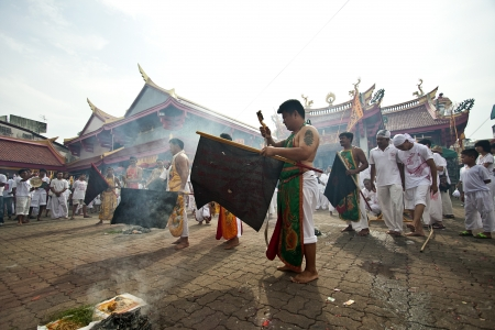 appease: PHUKET, THAILAND - OCTOBER 20, 2012 : A Taoist devotee participates in the Phuket Vegetarian Festival on Oct 20, 2012 in Phuket, Thailand. The festival ritual mortification is practiced to appease the Gods.
