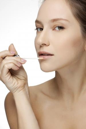 applying lipstick: Close-up portrait of a beautiful young woman applying lipstick.