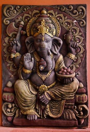 god bless: Sculpture of Gannesa hindu god on the orange wall  Stock Photo