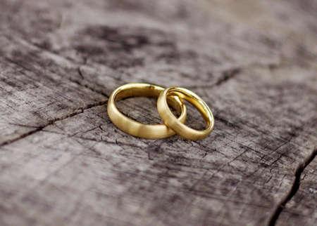 anillos de boda: Un par de anillos de boda en un bloque de madera Foto de archivo