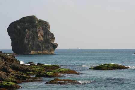 Sailboat Rock above the ocean, made by coral photo