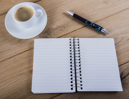 image of coffee cup with notebook and pen. photo