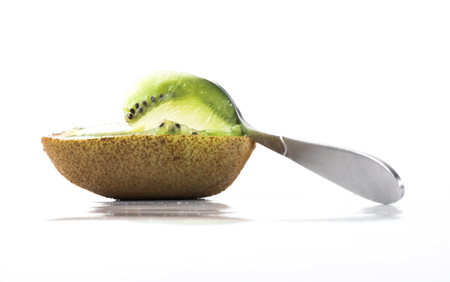 completely: Image of green kiwi and spoon isolated close up. Stock Photo