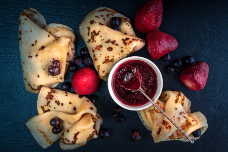 Russian pancakes with jam, black currant and strawberries 写真素材