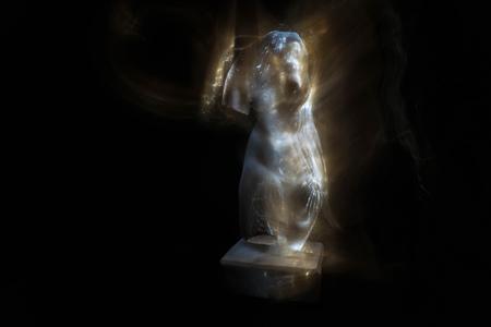 Gypsum torso of Venus de Milo on a black background