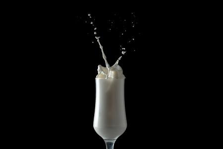 Milk shake splashes from a glass. Isolated image on black background. Imagens