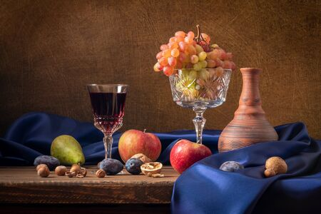 Still life with fruit and red wine. Grapes, apples, pear, plums, nuts and blue drapery. Banque d'images