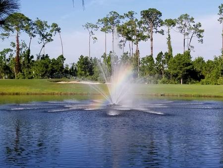 Fountain with a rainbow on a golf course