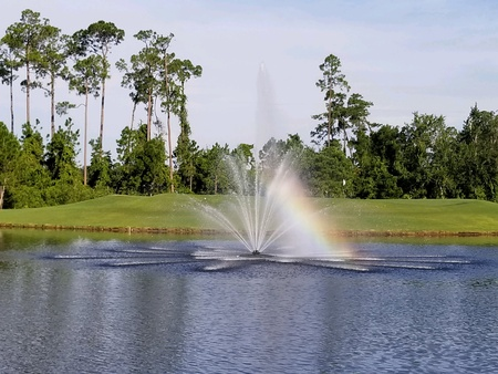 Sun casting a rainbow on a fountain in a pond on a golf course Imagens