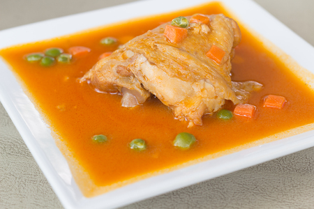 Chicken Thigh Stew on White Ceramic Plate, Idea Concept for Menu Background.