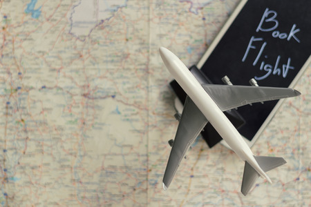 Airplane Model on Smart Mobile Phone with Word Book Flight on Screen on Map Background, Copy Space, Idea Concept for Fly Trip Travel Plan by Internet. Intently focus on airplane model.