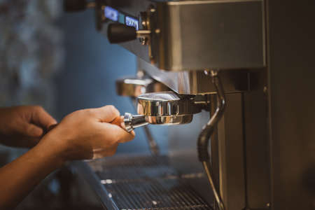 The barista is brewing Dirty coffee from the machine.