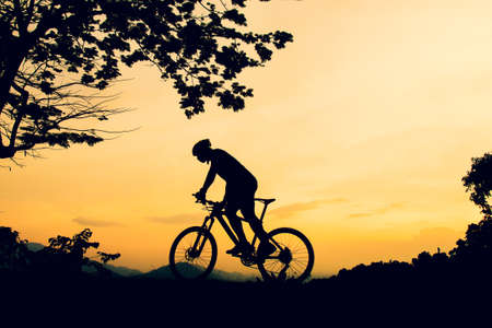 A silhouette of a mountain biking practicing bicycles on a high mountain