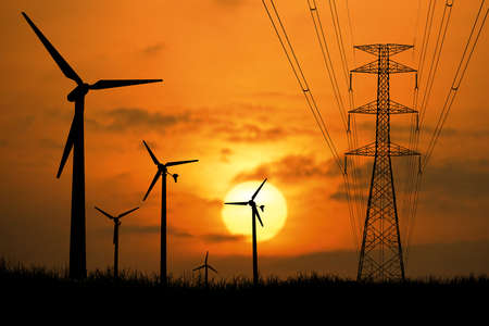Silhouettes of wind turbines and high-voltage poles in a field at sunset.