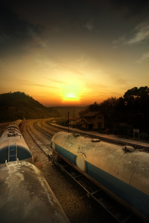 Set of tanks with oil and fuel transport by rail in orange sunset photo