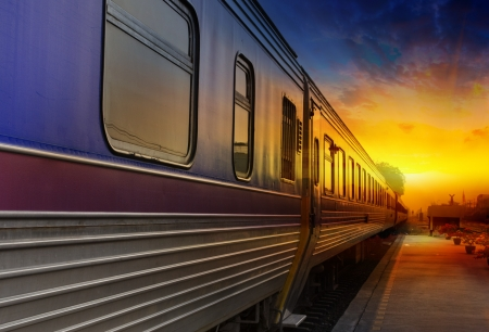 estacion tren: Tren pasando por la puesta del sol de color naranja
