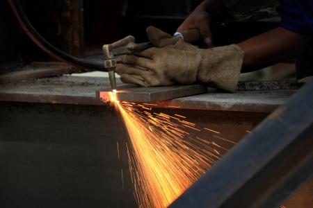 metal cutting: worker weld metal in factory and sparks