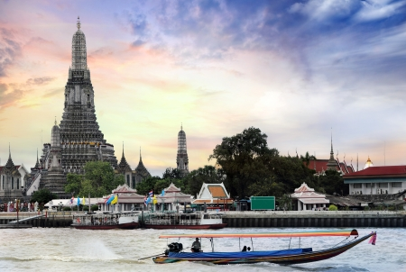 Twilight view of Wat Arun across Chao Phraya River during sunset in Bangkok, Thailand