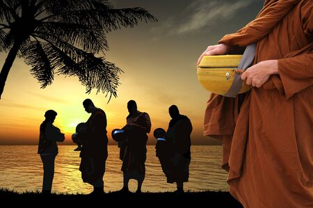 Silhouettes of monks on the beach, Thailand photo