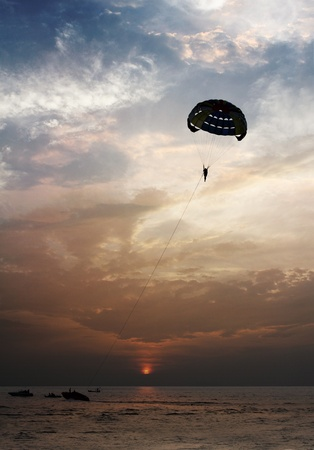 A beautiful background of a parasailing parachute on the backdrop a sunset on an evening sky  photo