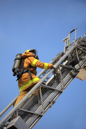 Firefighter ascends upon a one hundred foot ladder. photo