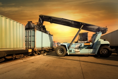 Crane lifting up container in sunset photo