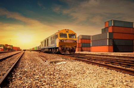 entrenar: Cargo plataforma del tren al atardecer con contenedor Foto de archivo