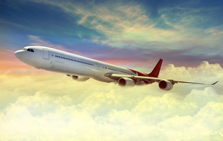Airplane flying above sky at sunset Stock Photo