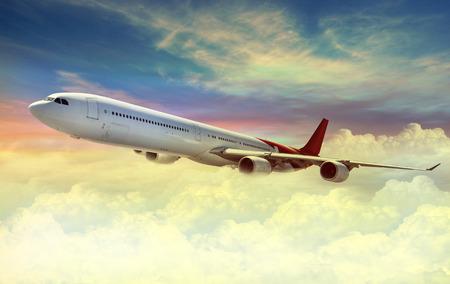 Airplane flying above sky at sunset Standard-Bild