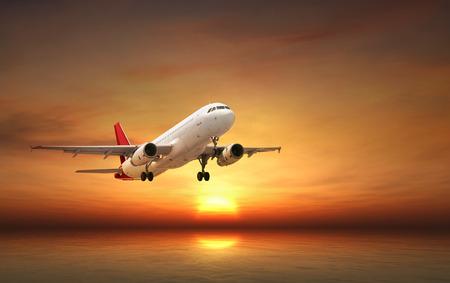 comercial: Avión volando sobre el mar tropical al atardecer Foto de archivo