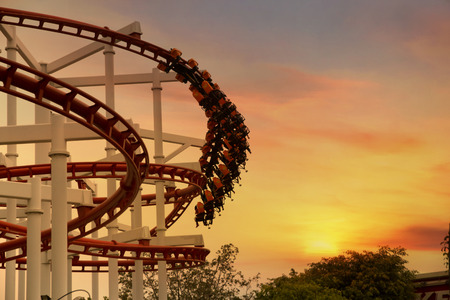 playground ride: Roller Coaster loops in the sunset