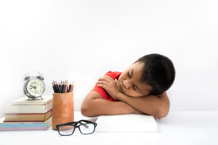tired child lying and sleeping on the books photo