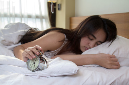 snoozing: Woman turning off the alarm clock Stock Photo